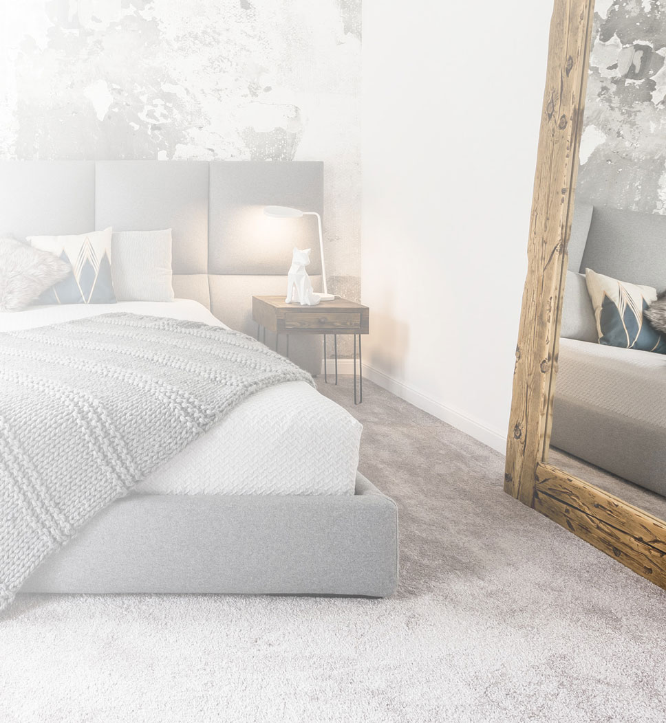 Ein modernes Landhausschlafzimmer mit kuscheligem grauem Teppich und rustikalem Holzspiegel.