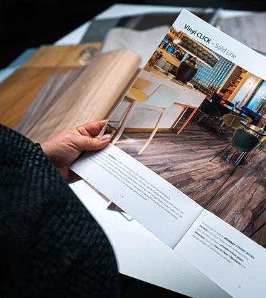 Eine Architektin blättert in unserem WEARMAX-Flooring-Designbödenkatalog und hat viele Bodennuster.