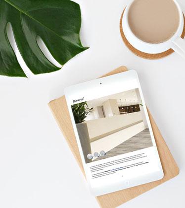 Tisch mit Kaffee, Monstera und Tablet mit unserem WEARMAX Flooring Online-Bodenbelagskatalog